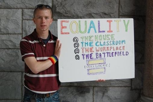 Bradley Manning holds a sign for equality.